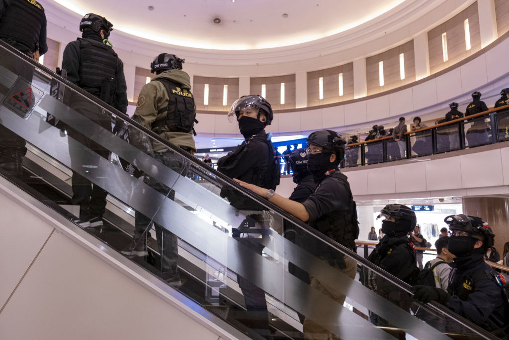 Riot police ride an escalator as they patrol the Harbour City shopping mall in the Tsim Sha Tsui district of Hong Kong, China, on Tuesday, Dec. 31, 2019.