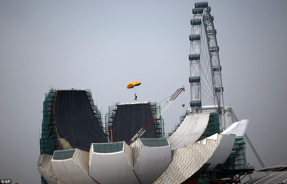 A skydiver parachutes pass the Singapore Flyer and Marina Bay Sands casino resort as part of the venue